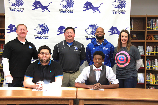 RLT Athletes Sign With Colleges. They are smiling at camera while posing with their coaches and principal.