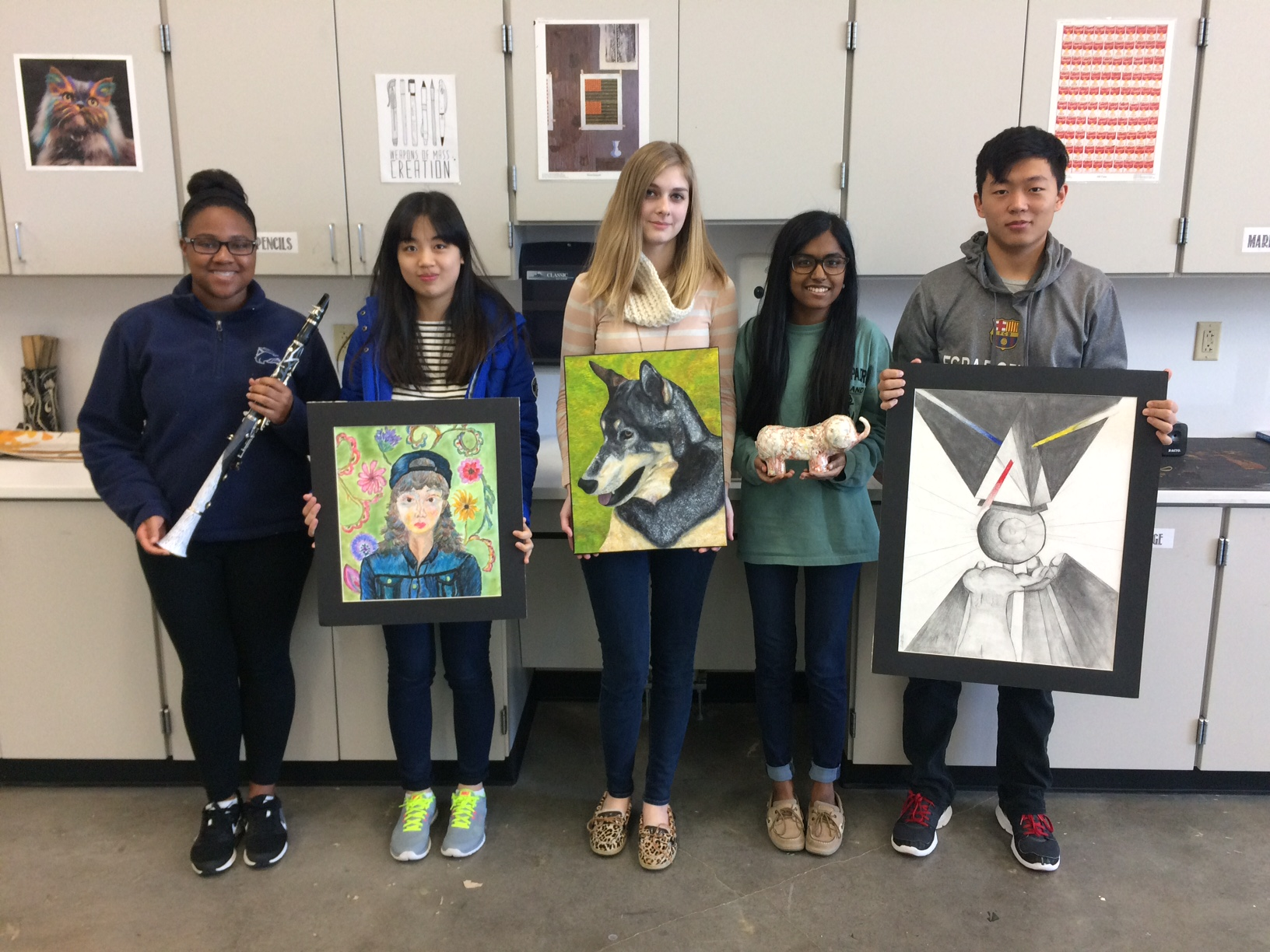 RHS Fine Arts students pose with their art, displaying a clarinet, a sculpture and flat artwork