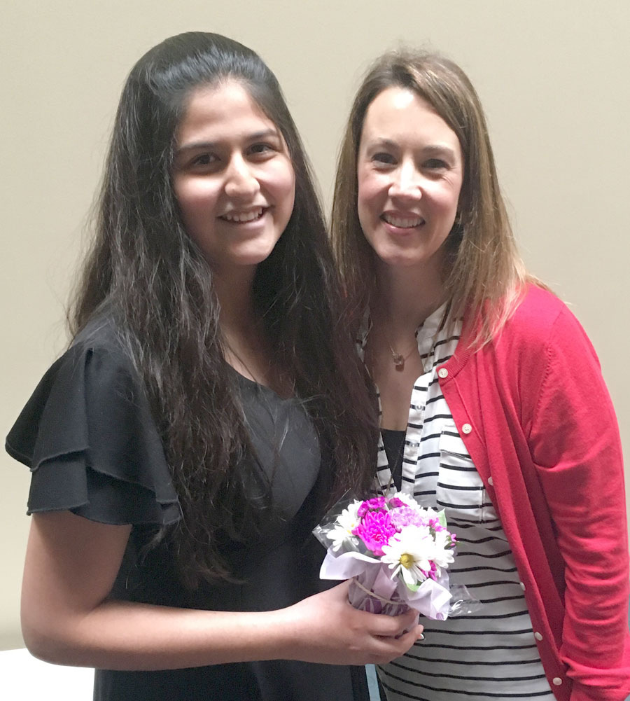 Student Alex Fresnillo smiles with RLT Principal Brooke Puricelli while holding a small bouquet of flowers.
