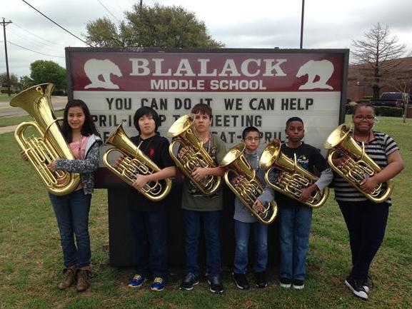 6 students from Band in front of the Blalack Middle School sign