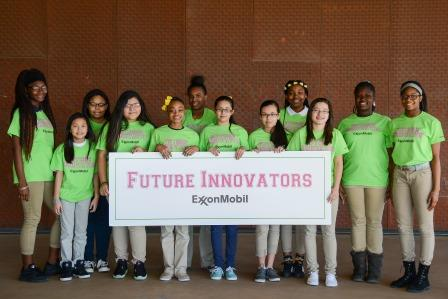 A group of female students holding a sign that says Future Innovators, Exxon Mobile