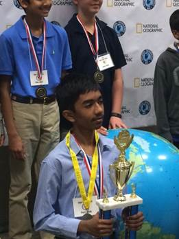 7th grade student, Pranay Varada holding his trophy for winning the State Geography Bee.