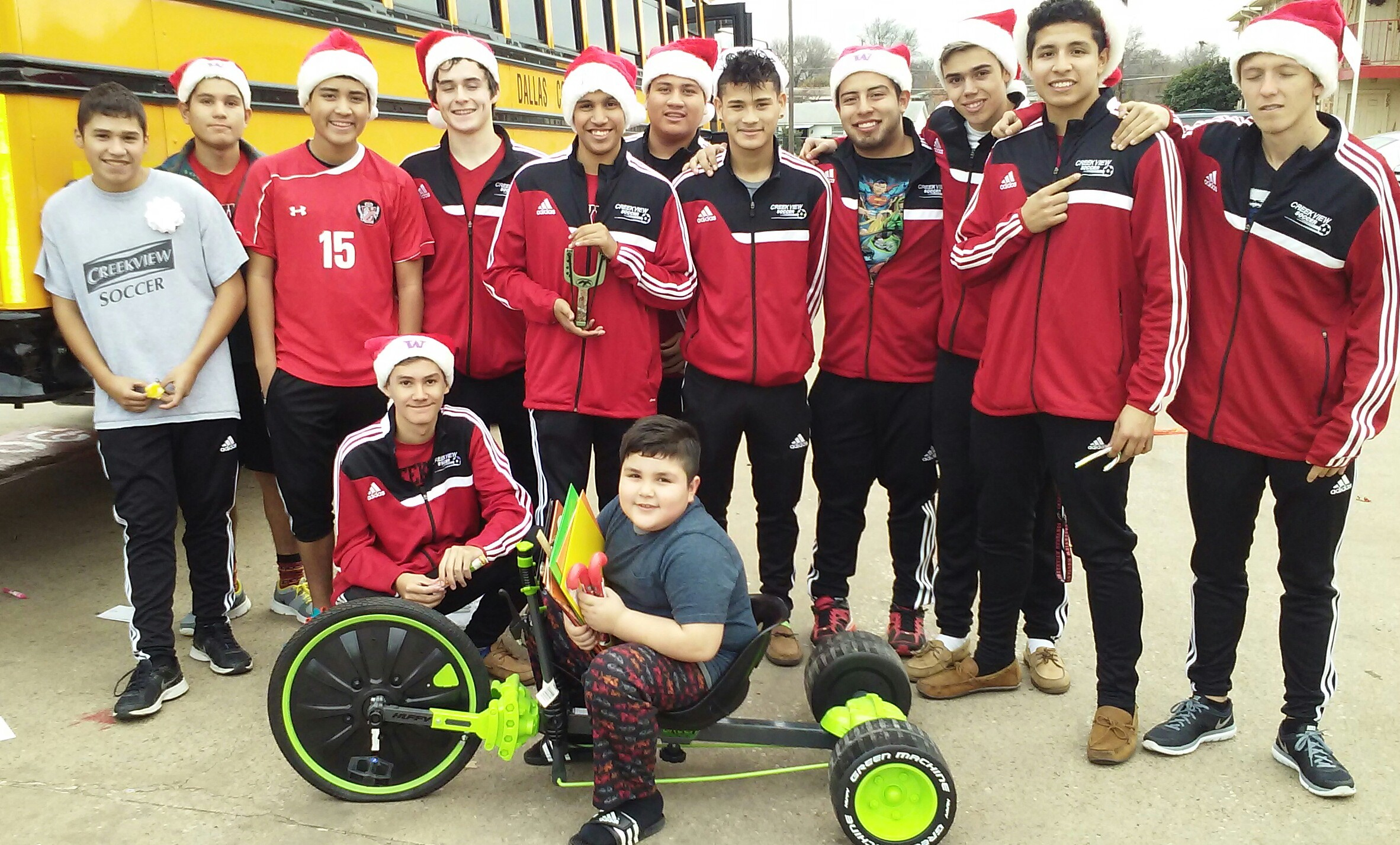 soccer team of creekview high school giving a child a tricycle