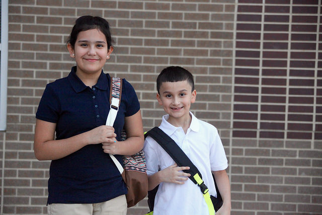 a girl and a boy student standing in front of las colinas elementary with their backpacks on