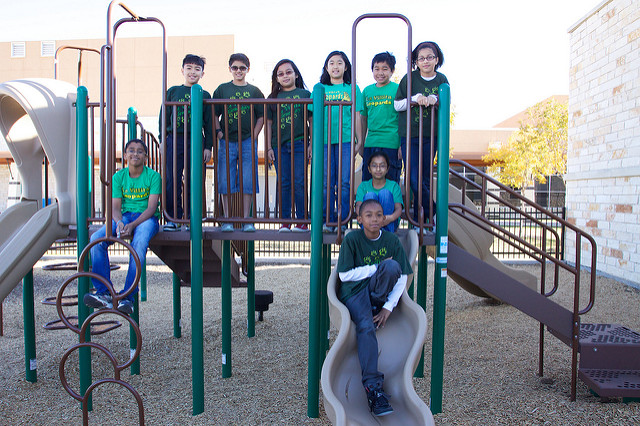 9 students posing for a picture on a playground with green shirts.