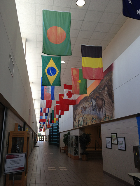 a hallway in the school with various flags hanging from the ceiling