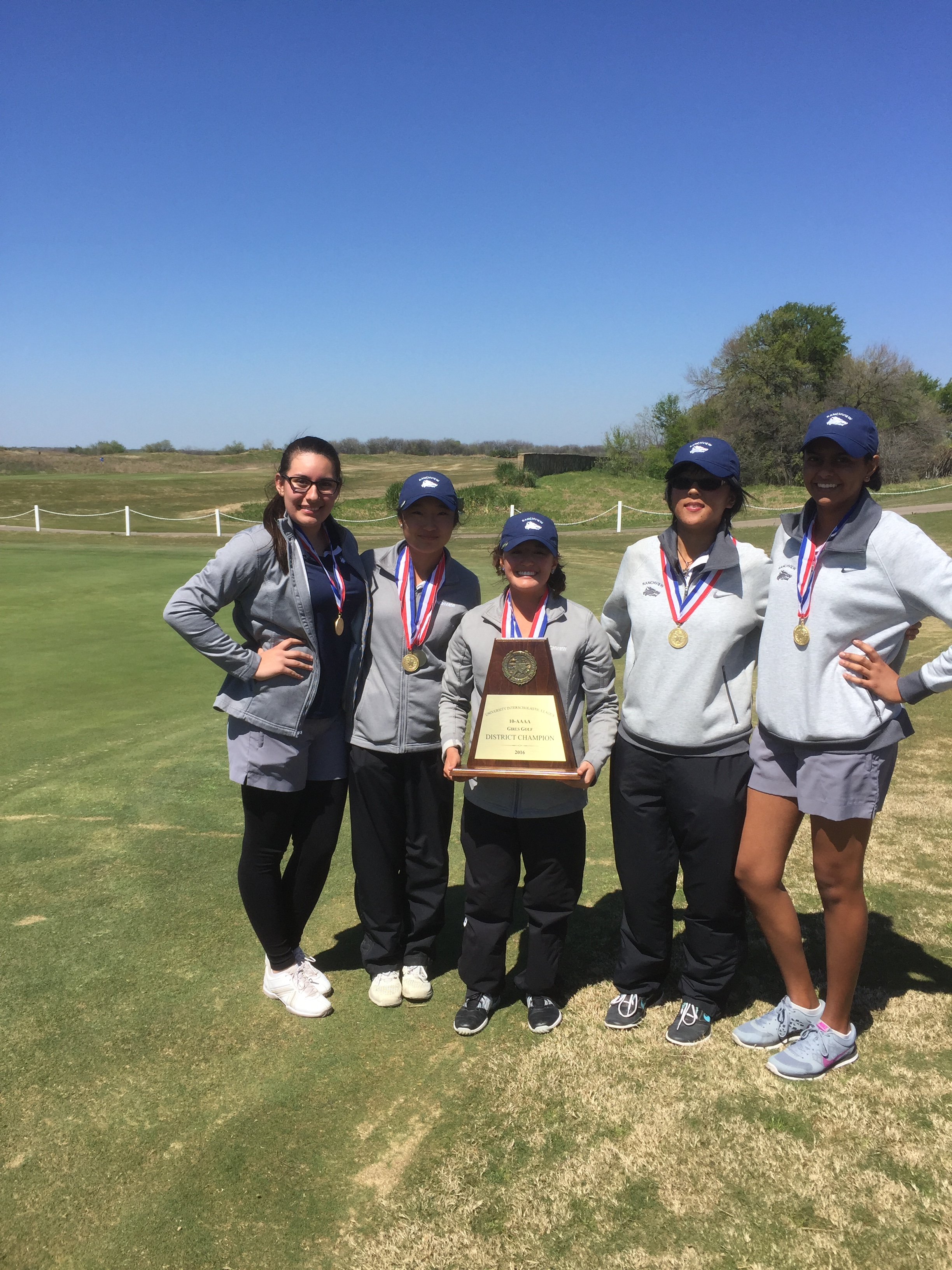Girls Golf team with medals and holding a trophy