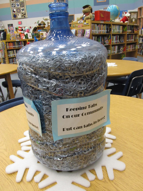 a liter water jug full of can tabs with a sign on it that says Keeping tabs on our community, put can tabs in here!