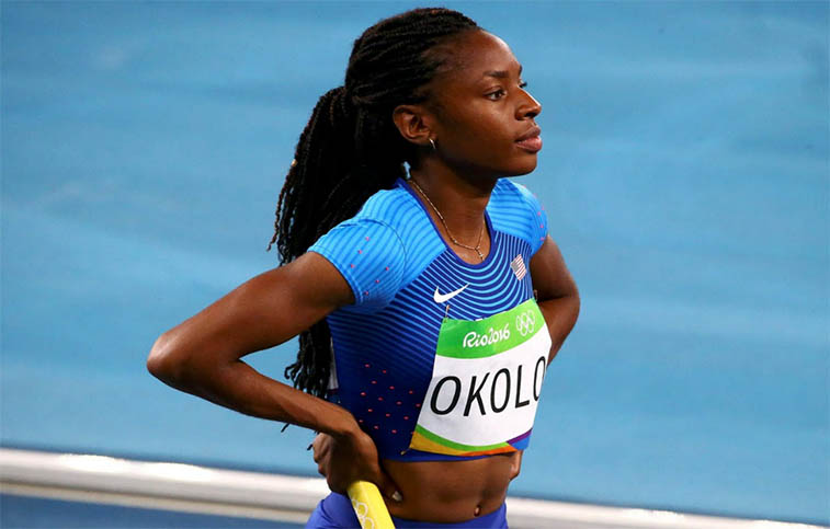 U.S.A. track star Courtney Okolo stands on the track during the Rio Olympics in 2016. She is wearing a blue and light blue track outfit as she holds a yellow batton