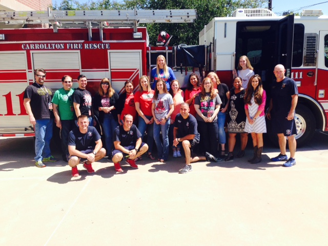 Staff of perry middle school with the fire department posing in front of a fire truck