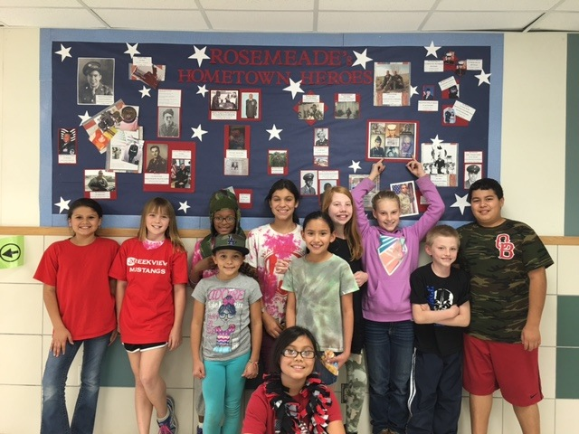 A group of students in front of a banner with pictures that says Rosemeade's Hometown Heroes
