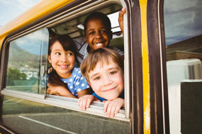bus routes - 3 children smile as they peer out a school bus window