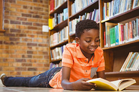 African American child laying down on the library floor reading a book with a yellow cover