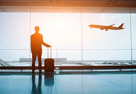 man at airport with luggage watch planes take off
