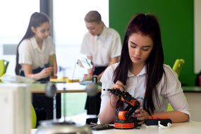 school girl working on a robot arm project as two other students are in the background slightly blurred