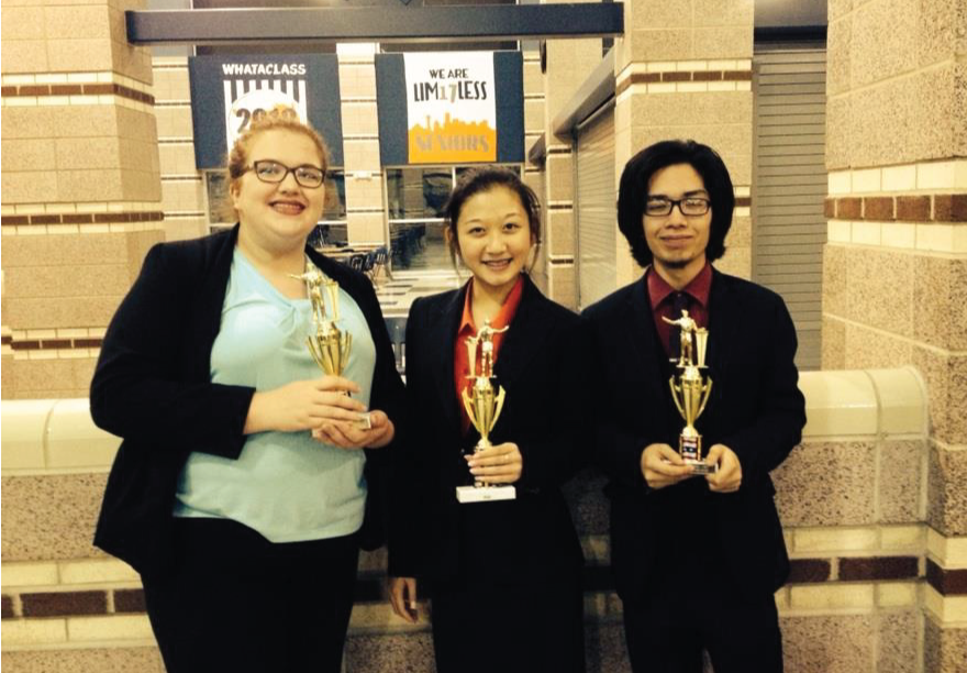 Debate team holding their trophies.