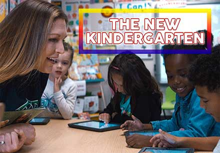 young kindergarten teacher in the classroom with her students as they interact with their ipads